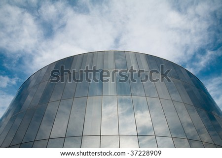 Glass round building with cloudy sky reflecting.