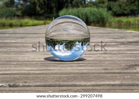 Glass sphere picture in nature with blue sky / Glass ball - stock photo