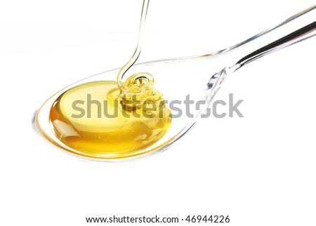 glass spoon with flowing honey
