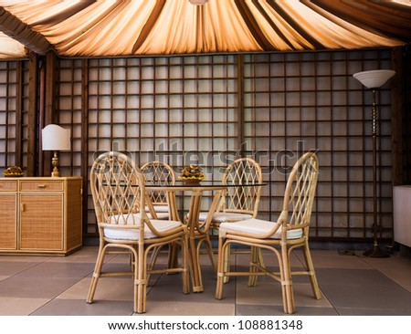 Glass table with wickler chairs in an elegant interior - stock photo