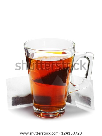 Glass tea cup and tea bags on white background