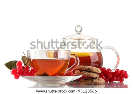 Glass teapot and cup with black viburnum hips tea isolated on white