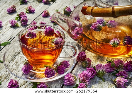 Glass teapot and cup with clover on old wooden table. - stock photo