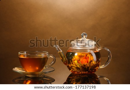 glass teapot and cup with exotic green tea on wooden table on brown background - stock photo