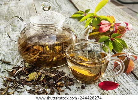 Glass teapot and cup with green tea on old wooden table. - stock photo