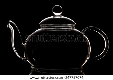 Glass teapot isolated on black - stock photo