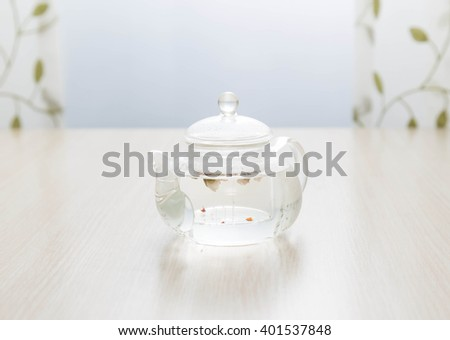 Glass teapot of invigorating fresh aromatic tea on a wooden table