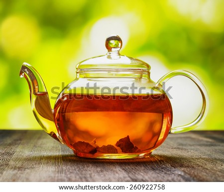 Glass teapot of invigorating fresh aromatic tea on a wooden table and on natural background. - stock photo