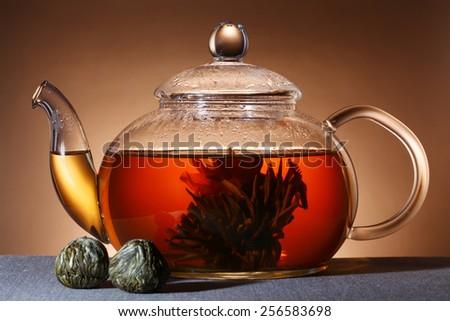 Glass teapot with black tea - stock photo