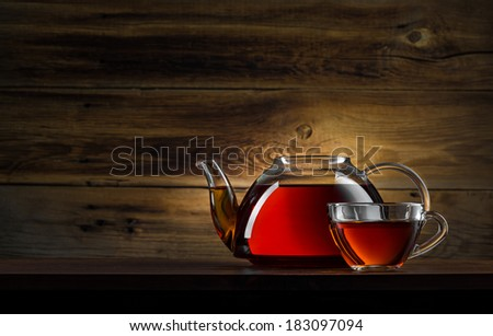 glass teapot with black tea on wooden background - stock photo