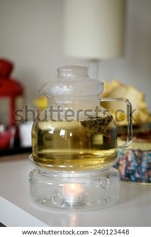 Glass teapot with blooming tea flower inside against home background - stock photo