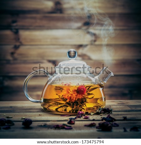 Glass teapot with blooming tea flower inside against wooden background  - stock photo