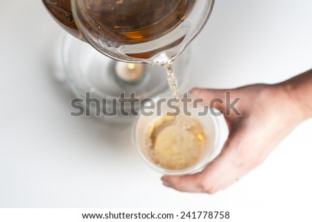 Glass teapot with blooming tea flower inside. Pour tea into a cup. - stock photo