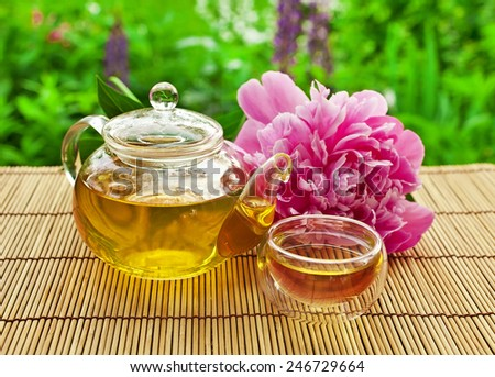 Glass teapot with glass cup and peony flower - stock photo