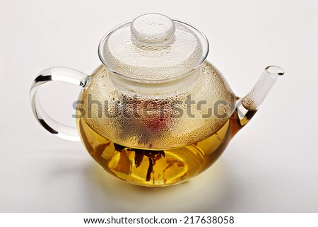 Glass teapot with green tea isolated on white background - stock photo