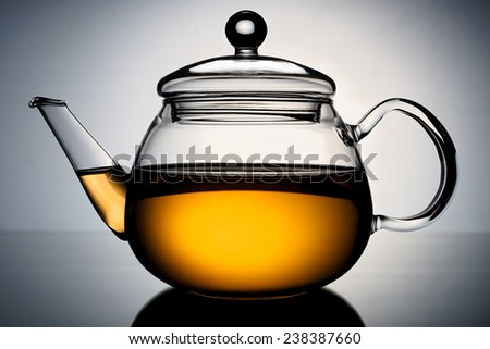 Glass teapot with the infusion of tea in the light gradient background. - stock photo