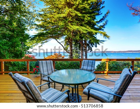 Glass top table with striped chairs on a wooden walkout deck of Modern beige house. Perfect water view. Northwest, USA
