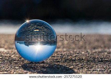 Glass transparent ball on dark background and grainy surface. Texture, outdoors - stock photo