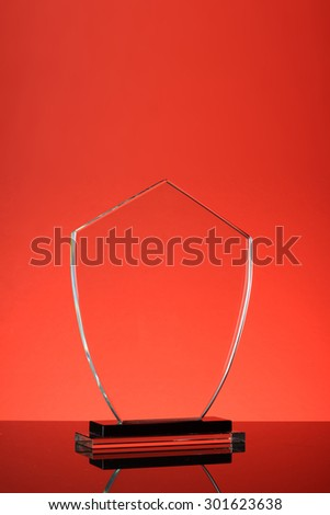 glass trophy in red background - stock photo