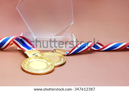 glass trophy with old gold medal in brown background, blank face for text : concept to the winner