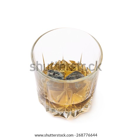 Glass tumbler filled with bourbon whiskey and granite cooling stones isolated over the white background - stock photo
