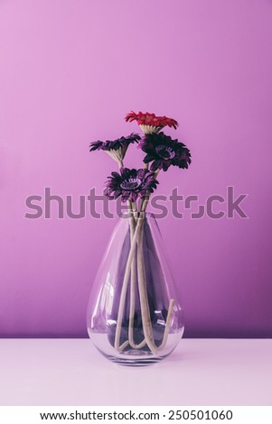 Glass Vase with Artificial Flowers Over a Violet Wall - stock photo
