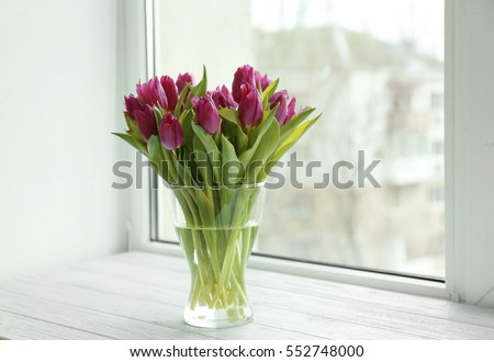 Glass vase with bouquet of beautiful tulips on windowsill