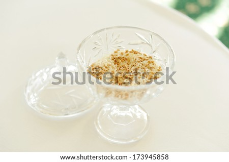 glass vase with wedding rings in grain - stock photo