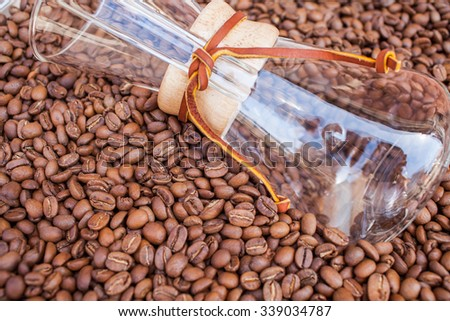 Glass vessel dip in pile of coffee beans. Background