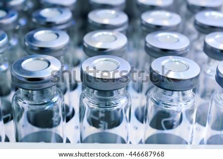 Glass vials for liquid samples. Laboratory equipment for dispensing fluid samples. Shallow depth of field. - stock photo
