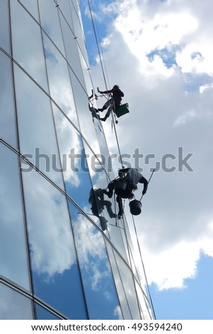 Glass wall cleaning. Workers washing windows in the office building