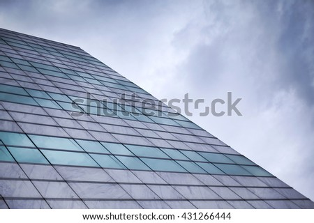 Glass wall of a building facade and cloudy sky