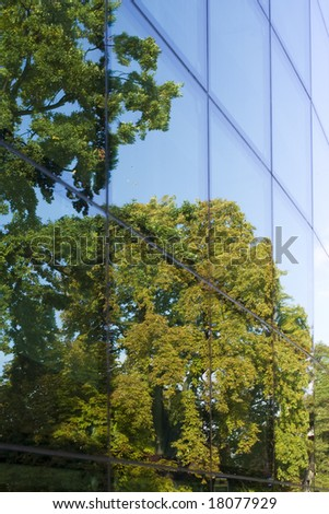 glass wall reflecting several trees and a blue sky