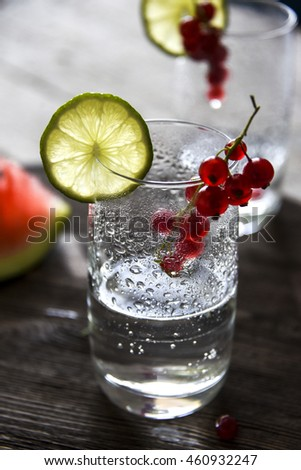 Glass, water, lime, red currant, clear drink on the table