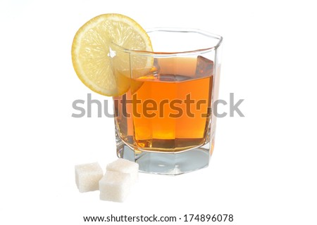 Glass with a slice of lemon filled with lemon tea and refined sugar isolated on white