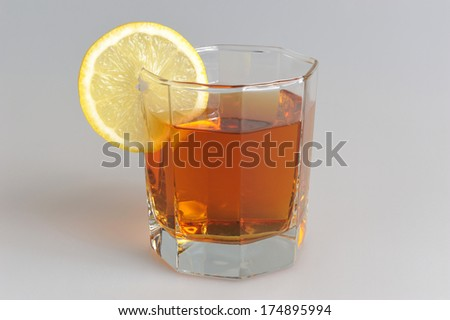 Glass with a slice of lemon filled with lemon tea on grey background