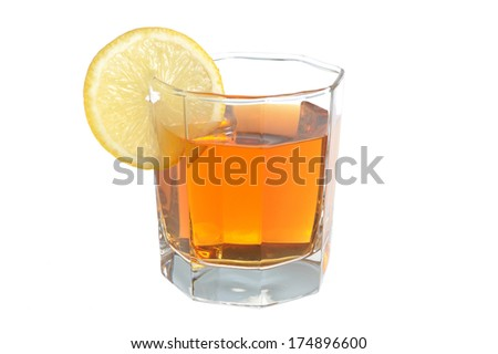 Glass with a slice of lemon filled with lemon tea on white background