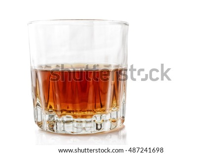 Glass with alcohol on a white background with reflection. Horizontal format. Indoors. Color. Photo.