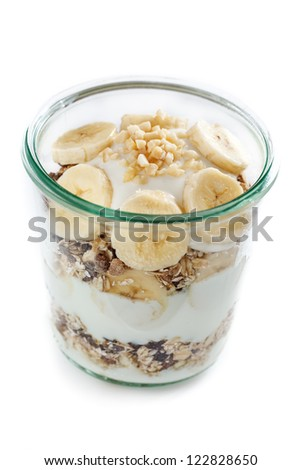 Glass with banana muesli and white background. - stock photo