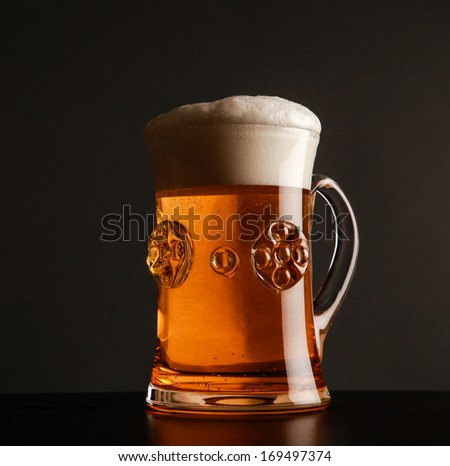 Glass with beer on dark background. - stock photo