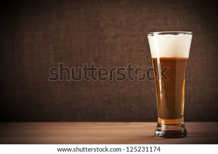 Glass with beer on the table - stock photo