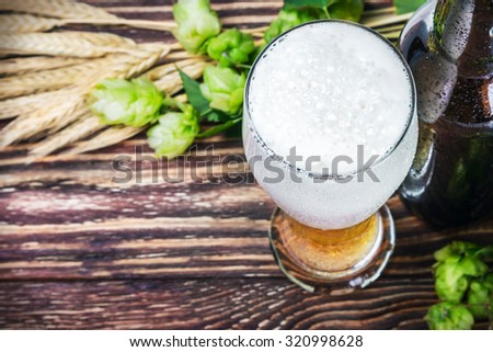 glass with Beer with hop on a wooden table. focus on beer froth - stock photo