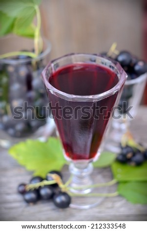 Glass with Black Currant juice in the country - stock photo