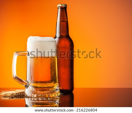 Glass with bottle of beer with blur orange background - stock photo