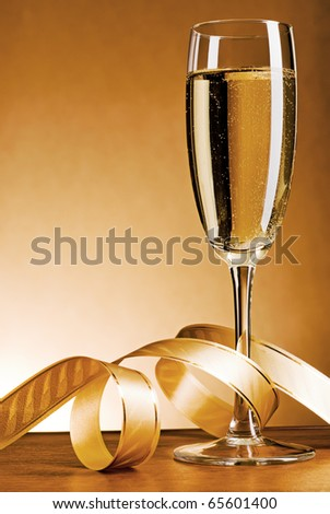 Glass with champagne and celebratory ribbon - stock photo
