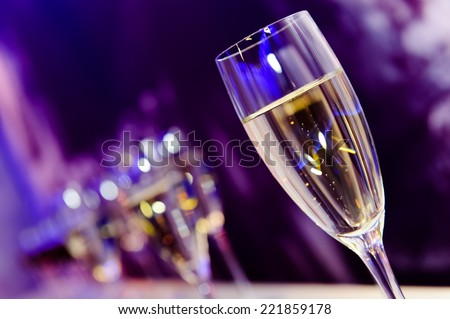Glass with champagne lit by nightclub lights on dark-purple background