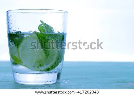 Glass with cocktail and ice with lime slice on table. - stock photo