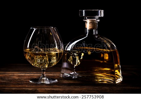 Glass with cognac on rustic wooden table - stock photo