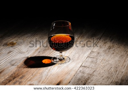 glass with cognac on the wooden table