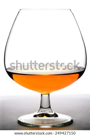 Glass with cognac on white background and wood base. Front view with copyspace. Close up shot. High resolution - stock photo